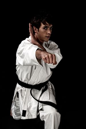 High Contrast karate young male fighter on black background.