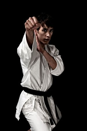 high contrast: High Contrast karate young male fighter on black background.