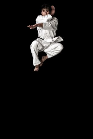 High Contrast karate young male fighter jumping on black background.  Stock Photo