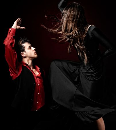 male dancer: High contrast Young couple passion flamenco dancing on red light background.