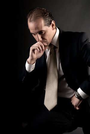adult businessman serious thinking sitting on dark background Stock Photo - 7501028
