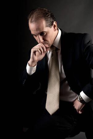 adult businessman serious thinking sitting on dark background Stock Photo