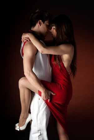 passion: Young couple dancing embrace passion romance on dark red light background.  Stock Photo