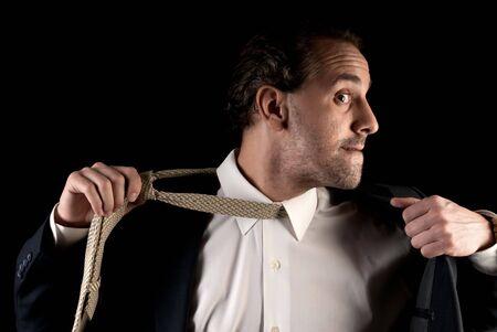 Adult businessman stressed pulling off tie on dark background