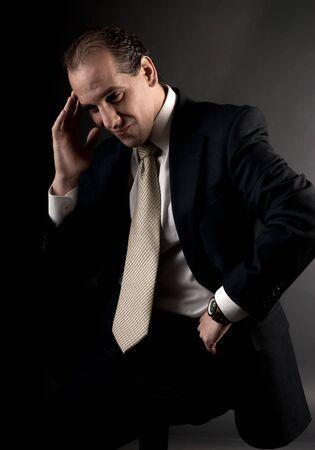 adult businessman serious thinking sitting on dark background Stock Photo - 7636293