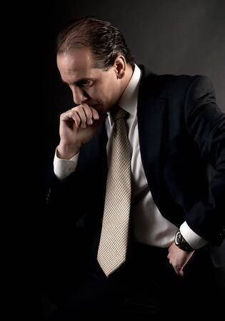 adult businessman serious thinking sitting on dark background Stock Photo - 7636296