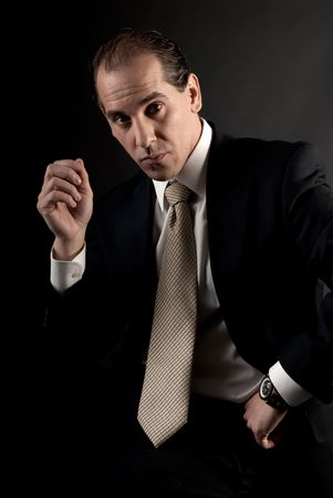 adult businessman well-dressed serious sitting looking at camera. photo