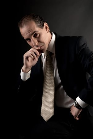 adult businessman serious thinking sitting on dark background Stock Photo - 7765354
