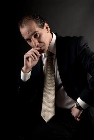 adult businessman serious thinking sitting on dark background photo