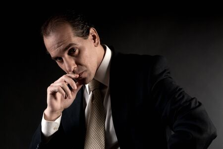 adult businessman serious thinking sitting on dark background Stock Photo - 7765356