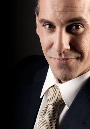 Adult businessman close-up portrait smiling on dark background.