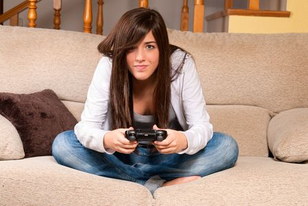 Young female playing video-games concentrating on sofa at home photo