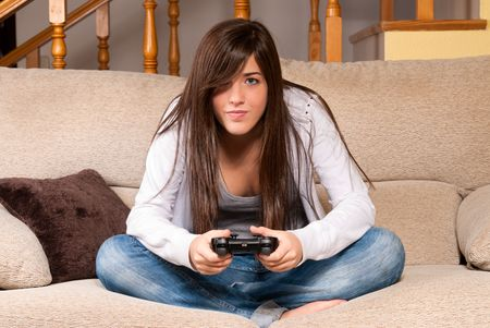 game room: Young female playing video-games concentrating on sofa at home
