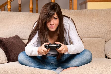 Young female playing video-games concentrating on sofa at home