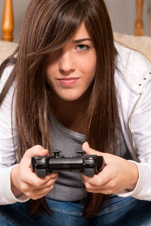 Young girl concentrating playing video-games close-up on sofa at home photo