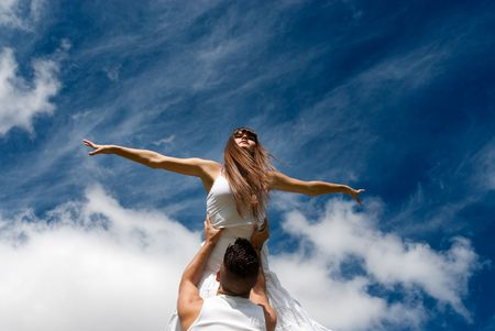 life support: young couple dancing on sky background, freedom and relax symbol