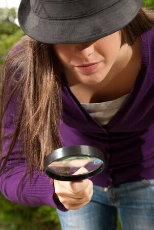 sagacious: young woman with magnifier glass and hat looking for something on outdoors background