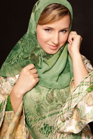 veiled: Young arab woman with veil close-up portrait on dark background Stock Photo