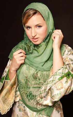 veiled: Young arab woman with veil standing on dark background Stock Photo