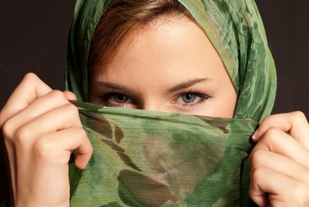 mystery of faith: Young arab woman with veil showing her eyes on dark gray background Stock Photo