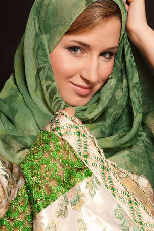cultural and ethnic clothing: Young arab woman with veil close-up portrait on dark background Stock Photo