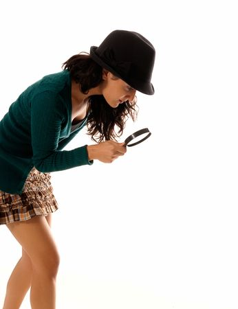 young woman with magnifier glass and hat looking for something isolated on white background photo