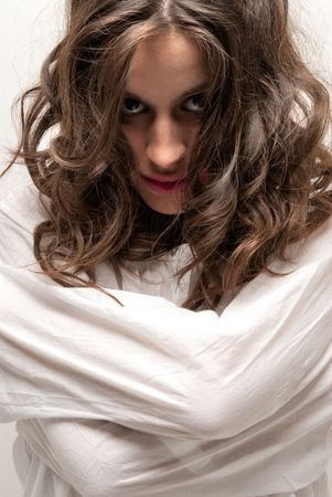 madness: Young insane woman with straitjacket looking at camera close-up portrait