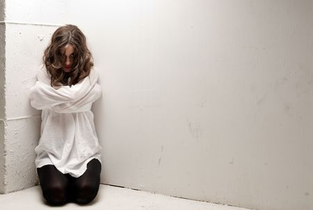 Young insane woman with straitjacket on knees looking at camera  Stock Photo - 8084990