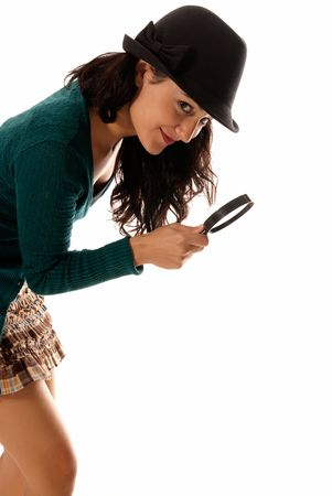 sagacious: young woman with magnifier glass and hat looking for something isolated on white background