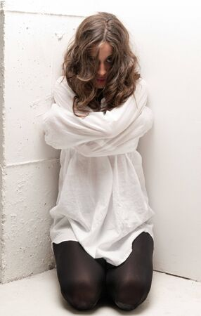 psychiatric: Young insane woman with straitjacket on knees looking at camera