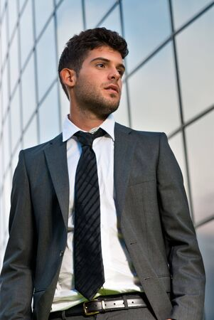 Young businessman looking to good future on modern building background photo