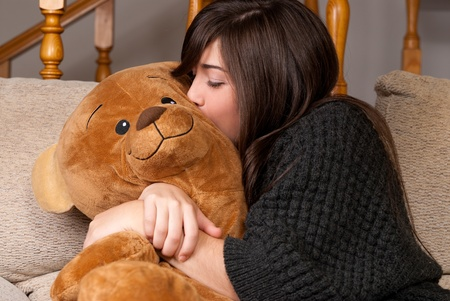 Young woman embracing and kissing teddy bear sitting on sofa close-up photo