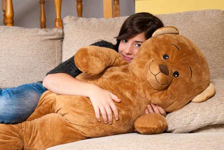 Young woman embracing teddy bear lying on on sofa photo