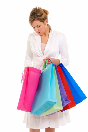 Young woman with shopping bags standing looking into bag isolated on white background photo