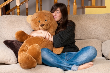 Young woman embracing teddy bear sitting on sofa photo