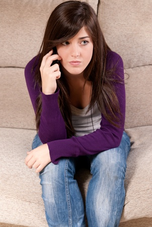 Young girl concerned talking by telephone bad news sitting on sofa photo