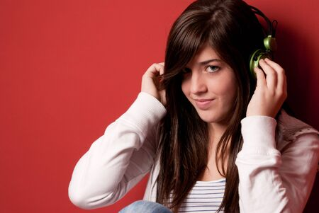 Young girl listening music with headphones on a red wall photo