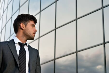 expectations: Young businessman looking good expectations on modern building background Stock Photo