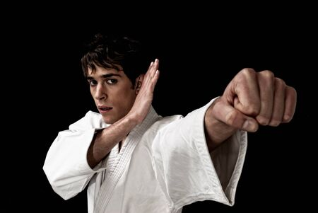 high contrast: Karate male fighter young close-up high contrast on black background.