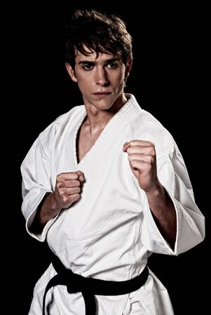 high contrast: Karate male fighter young high contrast on black background