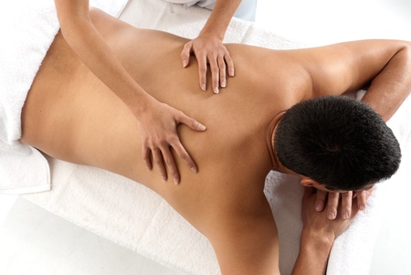 laying on back: Unrecognizable man receiving massage relax treatment close-up from female hands Stock Photo
