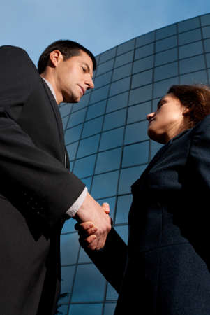 Handshake business man and woman on modern building background Stock Photo - 9682035