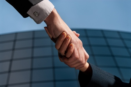 Handshake unrecognizable business man and woman on modern building background photo