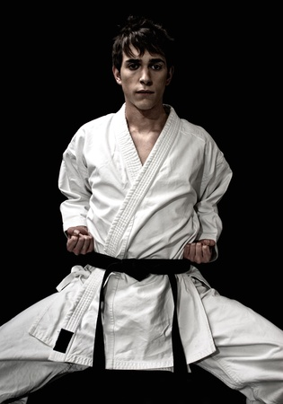 High Contrast karate male fighter on black background. On AdobeRGB. photo