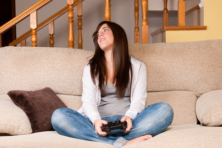 Young female lose playing video-games concentrating on sofa at home photo