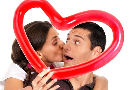 Young couple kissing through baloon heart surprise isolated on white backgroud