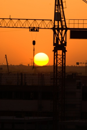 Crane silhouette over sun under construction symbol photo