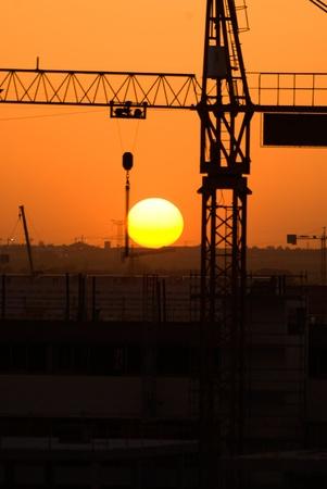 Crane silhouette over sun under construction symbol photo
