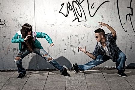 Young urban couple dancers hip hop dancing fight acting urban scene photo