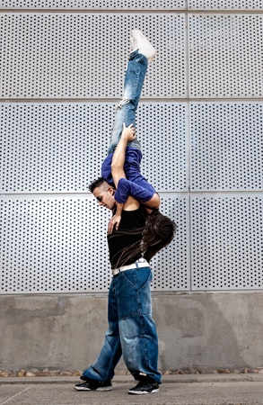 Young urban couple dancers hip hop dancing urban scene photo